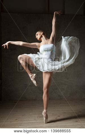 Portrait of professional ballet dancer in white dress performing in studio with arms up
