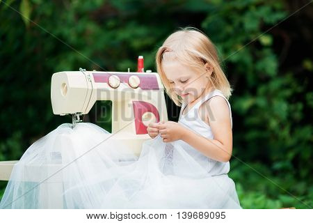 pretty happy blond child 4 years (a little girl) near the sewing machine
