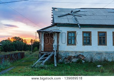 Village house with ruined porch on a beautiful sunset.