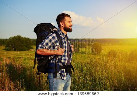 Side view of handsome bearded man with rucksack behind his back who is standing in the field and smiling during sunset
