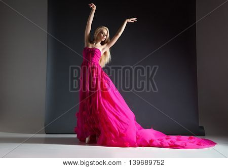 Elegant blonde woman posing in beautiful bright pink and long dress in studio on grey background.