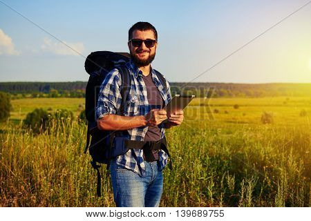 Handsome man in sunglasses with rucksack behind his back is standing in the field holding a data tablet in his hands and smiling