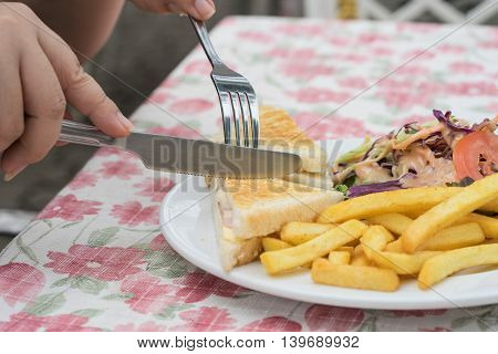 woman eating ham cheese sandwich serve in plate with french fried with knife and fork on white table in restaurant outdoor