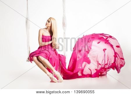 Portrait of blonde ballerina in ballet shoes and beautiful pink dress with flying skirt on swing