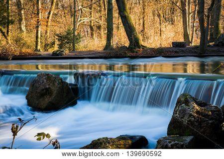 Flowing Soft Blue Water under Warm Orange Wiinter Forest