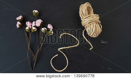 artificial rose flowers on a black wooden background