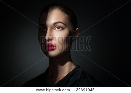 Fashion model with pink lips with half face covered with shadow.Isolate.Black background
