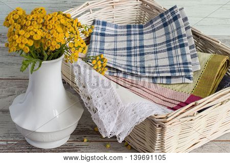 Canteens napkin in a wicker basket and a vase with flowers on a light wooden table.