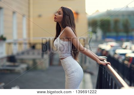 Sexy beautiful girl wearing white elegant dress posing outdoor at summer evening. Elegant woman portrait.