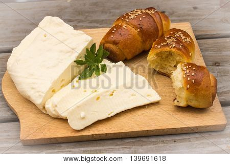Homemade croissant, white cheese and basil on wooden background