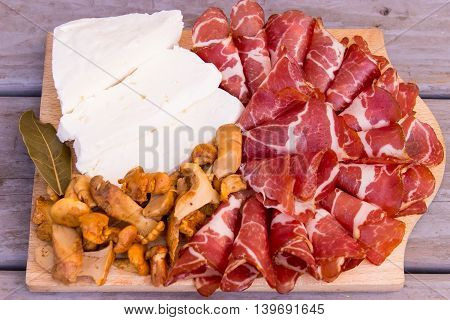 Prosciutto, marinated mushrooms and white cheese on wooden background