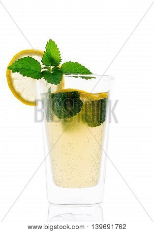 Homemade lacto-fermented refreshing drink with lemon slices and sprigs of mint and lemon balm.