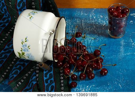 Still life with cherry glass and enamel the can. On a blue background.