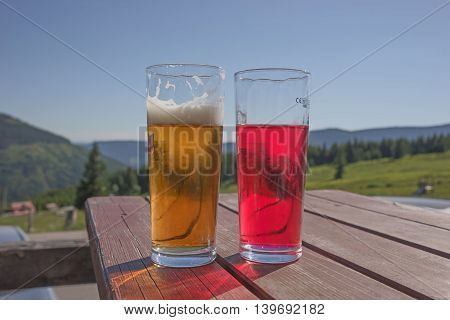 Beer and red lemonade on the table in the restaurant, mountains in the background