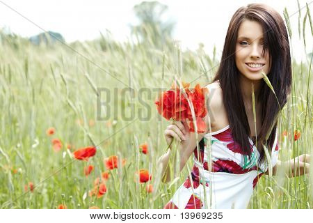 Summer girl running in poppy field