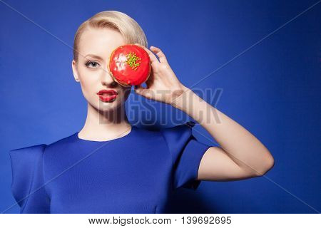 Portrait of young pretty model with red lips peeping out of bright donut on blue background