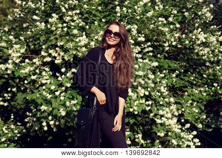 Happy smiling girl posing against green bushes with white blooming flowers. Stylish girl wearing black blouse and sunglasses