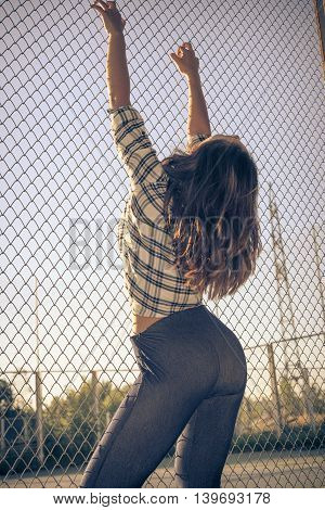 Young beautiful woman holding wire mesh with hands fit and beautiful body. Fashion concept. Special toned photo