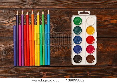 Assorted colors marker pens and pencils with watercolors on dark wooden background