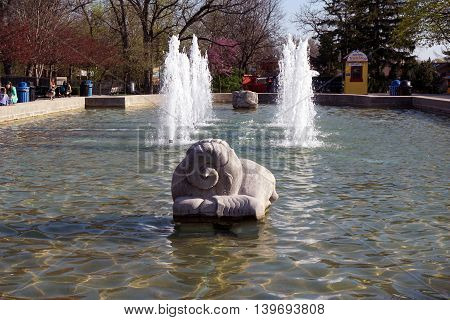 BROOKFIELD, ILLINOIS / UNITED STATES - APRIL 23, 2016: A sculpture of a ram sits in a fountain at the Brookfield Zoo.