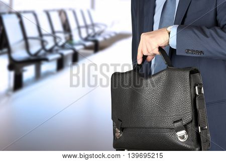 businessman holding leather briefcase checking time on his watch at office