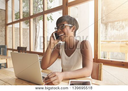 Portrait Of Young Charismatic African Adult Woman Laughing While Talking On Cellphone With Her Man,