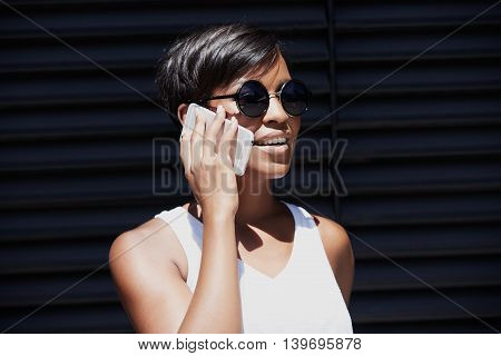 Attractive Successful African Female In Round Hipster Sunglasses Looking Into Distance With Cheerful