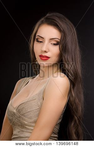 Young brunette lady in evening dress with beautiful make-up posing on black background