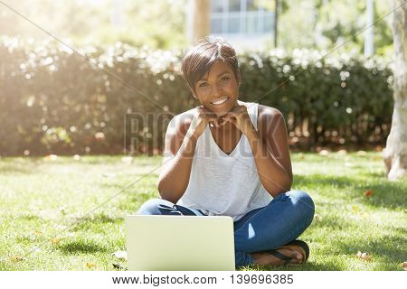 Close Up Portrait Of Young Cute African American Woman With Gorgeous Smile, Sitting On The Grass In
