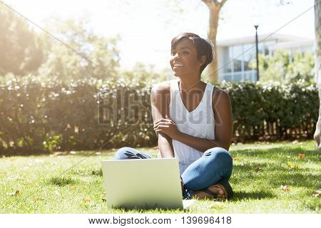 Happy And Cheerful Black Female With Short Haircut Sitting On The Grass, Smiling To Her Friends Appr