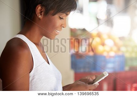 Profile Portrait Of Young Good-looking Dark Skinned Smiling Woman Leaning Against The White Wall, Ho