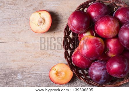 plums in basket on a dark wood background .
