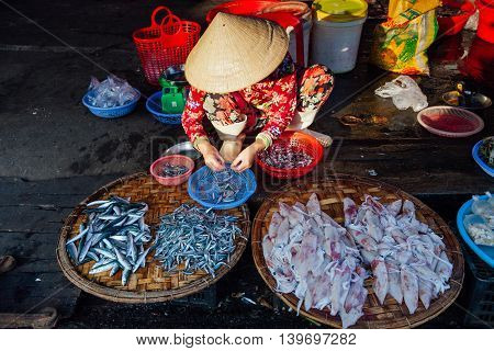 NHA TRANG VIETNAM - JULY 14: Vietnamese woman in conical hat sells fish at the morning market in Nha Trang Vietnam on July 14 2016.