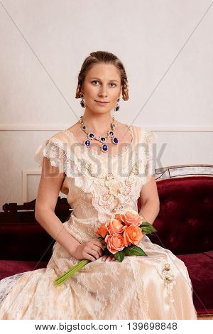 portrait of victorian woman sitting holding flower bouquet