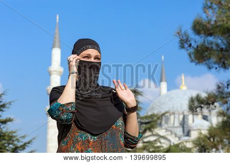 Portrait of beautiful Arabian Woman in traditional Muslim Clothing talking on Telephone gesturing Middle East Urban landscape with Mosque and Minarets on Background