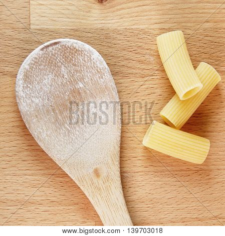 raw dried pasta on cutting board with wooden spoon