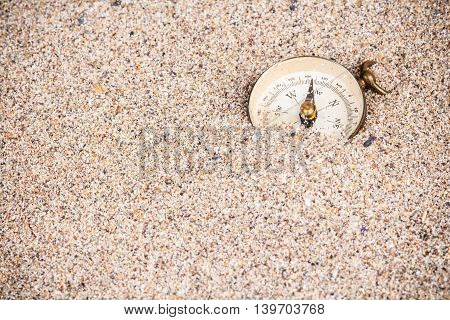 Adventure background with compass disappearing in sand