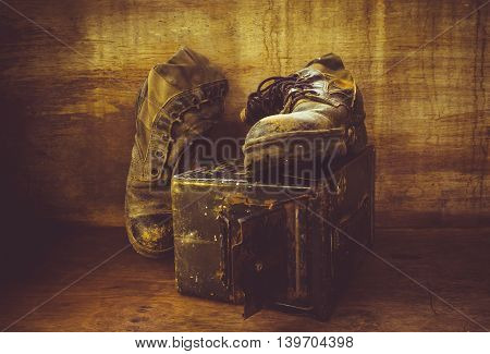 Still life with old jungle boot on iron bullet box
