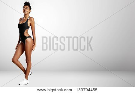 Young Pretty Woman In A Grey Studio Space In Swimsuit