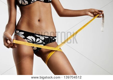 Woman With A Tape-measure On Her Leg On A Grey Background