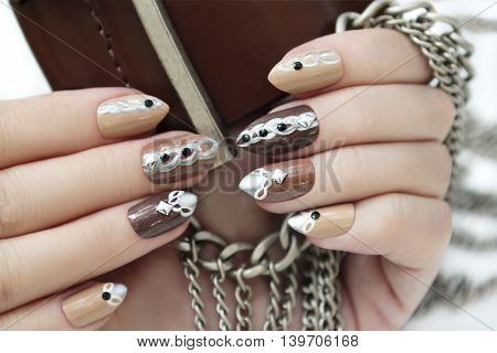Manicure in brown shades of nail Polish designed in the form of chains with rhinestones on a woman's hand.