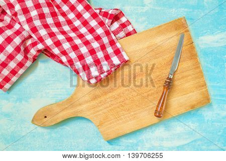 Rustic kitchen household objects top view of knife cutting board and table cloth