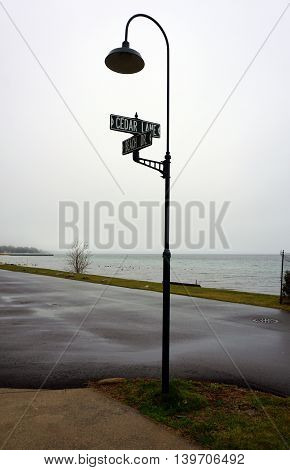 Street signs on a lamppost mark the intersection of Beach Drive and Cedar Lane in Wequetonsing, Michigan.