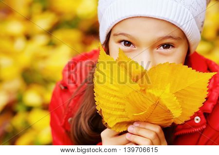 portrait of a beautiful teenage girl with yellow leaves in autumn