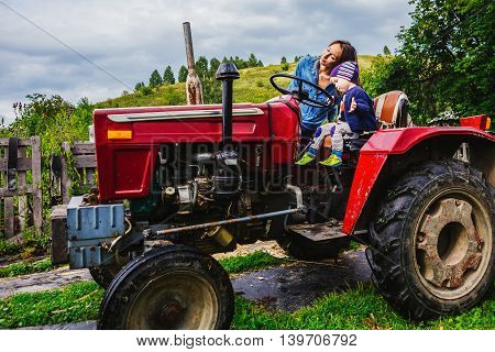 Mother and son sitting on a tractor in the village sunny day after rain red rural tractor
