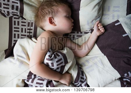 Little boy sleeping in the crib sleeping on his side in bed covered with a blanket morning room lighting