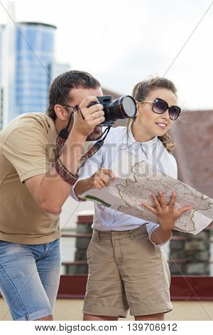 Travelling Concepts. Tourist Couple in Town Outdoors Taking PIctures Together. Happy Couple Vacation. Vertical Image