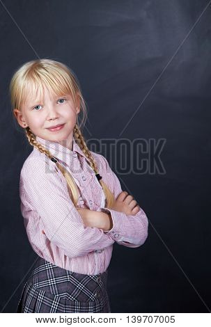 Portrait of a schoolchild on a background of a blackboard. School and education