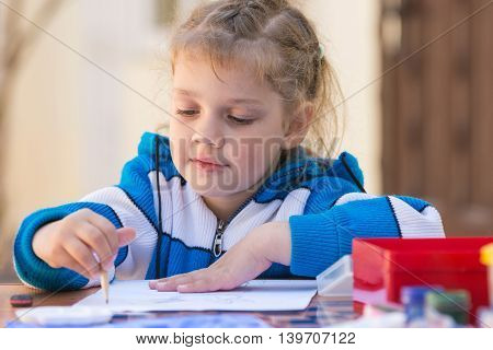 Pretty Girls Sitting At A Table In The Courtyard Of The House And Draws Pencil