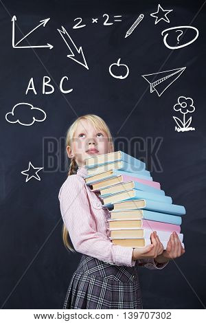 schoolchild with books in hand on background of a blackboard. School and education